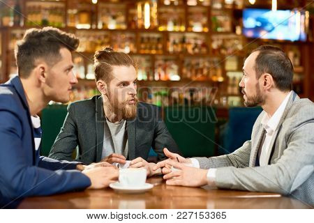 Three Hard-working Managers In Formalwear Discussing Ambitious Project While Sitting At Cafe Table A