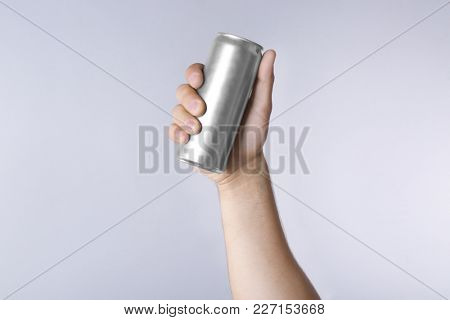 Male hand with aluminum can on light background