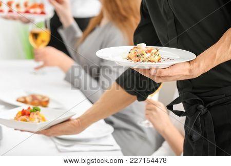 Waiter serving tasty dishes at restaurant