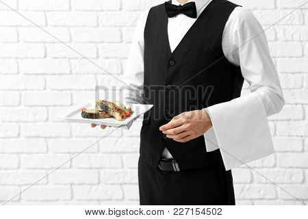 Waiter holding plate with fish and rice on brick wall background
