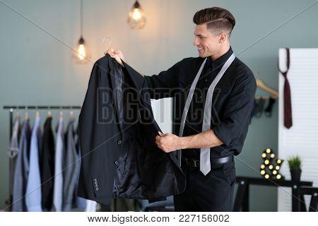 Man with new jacket indoors. Fashionable wardrobe
