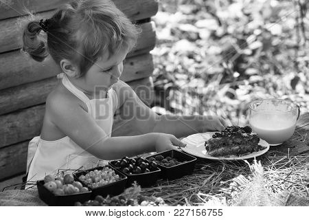 Cute Little Boy With Blond Hair Ponytail In White Pinafore Serves At Rustic Table With Fruit Cake Be