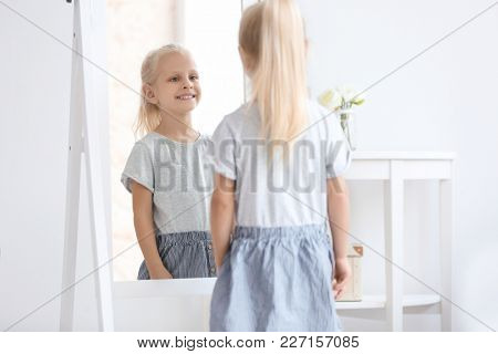 Cute little girl looking at herself in mirror indoors