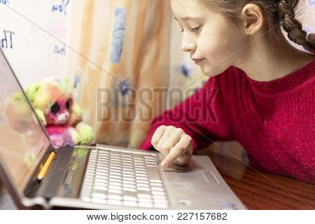 A Girl Of 8 Years Doing Homework On A Laptop.