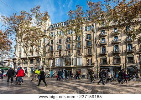 Barcelona, Spain - December 5, 2016: People Walk By At The Famous La Rambla Street In Barcelona, Spa