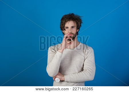 Man With Pills Has Uncombed Hair In Morning On Blue Background, Health And Medicine, Handover And He