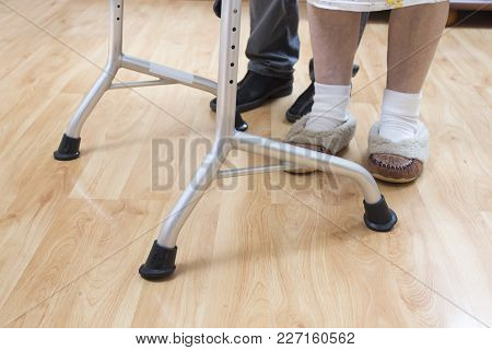 The Legs And Feet Of An Old Woman With The Wheels Of The Walker. Doctor Helping An Old Woman.