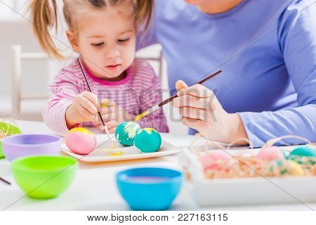 Mother And Daughter Coloring Eggs For Easter.