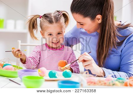 Happy Mother And Daughter Coloring Eggs For Easter.