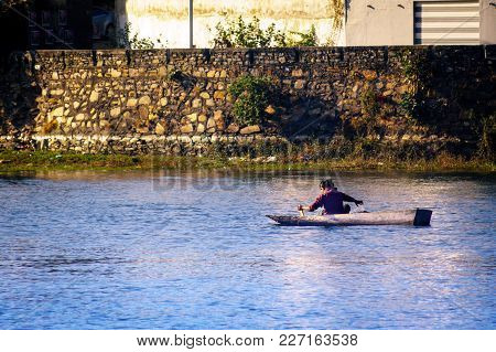 Udaipur, India - 25th Dec 2017: Fisherman On A Rowing Boat Fishing In The Shallow Waters Of Lake Fat