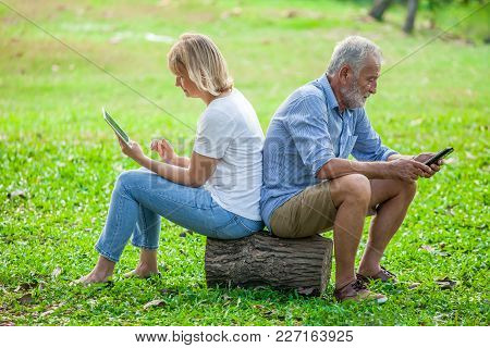 Elderly Couple Sitting Back To Back In A Park And Play Mobile Phone And Tablet