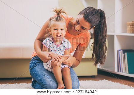 Happy Mother And Daughter Embracing In Their Home.