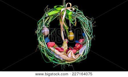 Easter Wreath On A Black Background, Braided From A Vine, With Colorful Ribbons And Hanging Eggs
