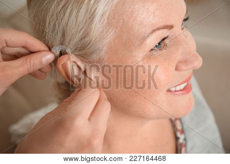 Doctor inserting hearing aid in ear of mature woman, closeup