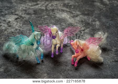 Three Pegasus Horse Toys On A Black Cement Background, Side View With Copy Space