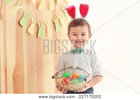 Cute little boy with bunny ears holding basket full of Easter eggs indoors