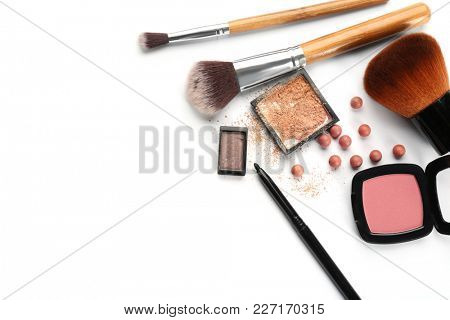 Decorative cosmetics and tools of professional makeup artist on white background