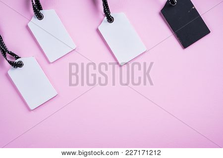 Empty White And  Black Tags In A Row On Pink Background. Top View. Mock Up Sample. Blank Price Tag.