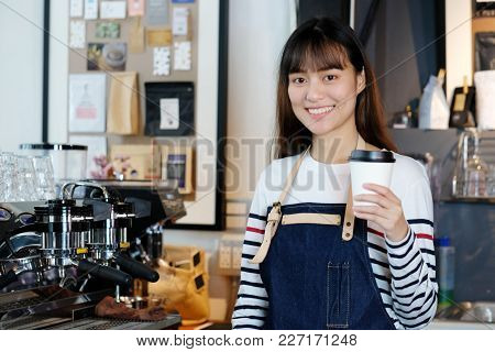 Young Asia Woman Barista Holding A Disposable Coffee Cup With Smiling Face At Cafe Counter Backgroun