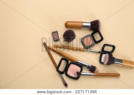 Decorative cosmetics and tools of professional makeup artist on color background