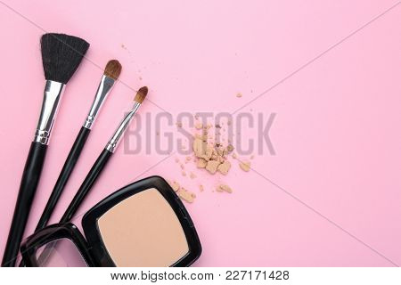 Facial powder and brushes of professional makeup artist on color background