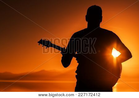 Guitar Playing At Sunset. Men With Acoustic Guitar During Scenic Sunset. String Instrument Theme