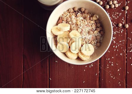Healthy Breakfast. Copy Space. Granola Bowl With Banana, Raisins And Nuts And On The Wooden Backgrou