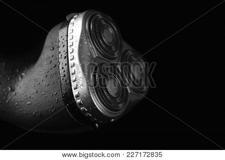 Electric shaver for man on black background