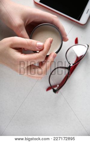 Woman holding jar with clay for hair over table