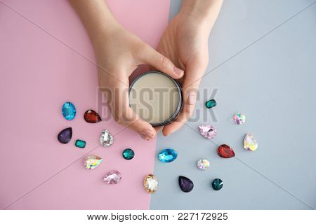 Woman holding jar with clay for hair on color background