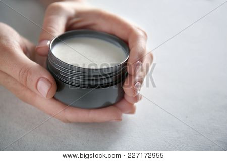 Woman holding jar with clay for hair on light background