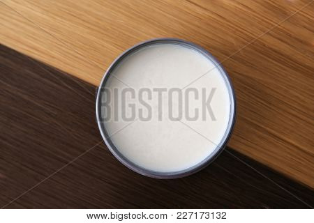 Jar with clay for styling on strands of blonde and brown hair