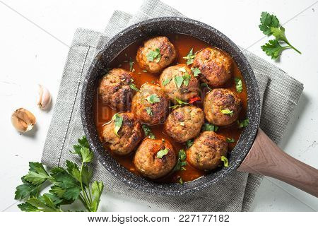 Meatballs In Tomato Sauce In A Frying Pan. Top View On White Background.