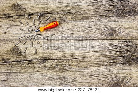 Screwdriver With Many Attachments On Wooden Backboard