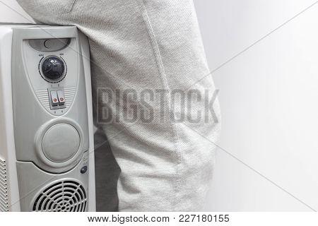 Unknown Man Sitting On Gray Oil Heater