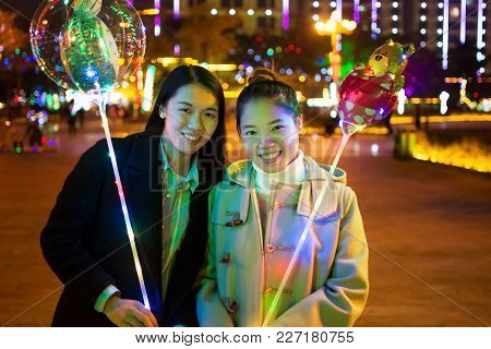 Friends With Illuminated Balloons In The City At Night