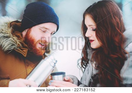 Guy And Girl Drinking Tea In The Snowy Forest