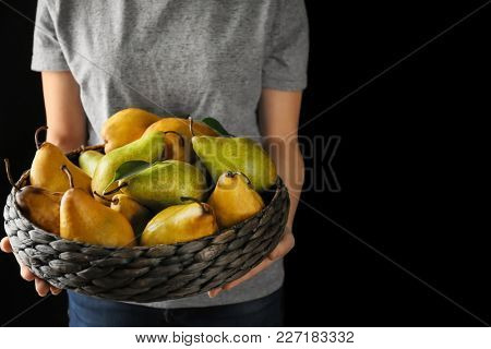 Woman holding basket with ripe pears on black background