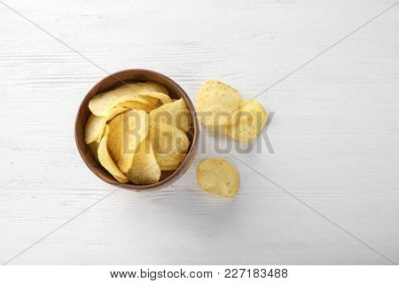 Potato chips in bowl on wooden table, top view