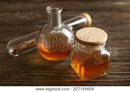 Vanilla extract in glassware and sticks on wooden table