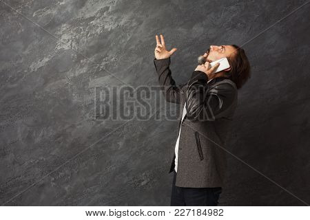 Stressed Businessman Talking On Phone, Looking Upwards In Despair. Job Problems Concept, Copy Space,