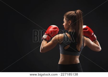 Back View Of A Gorgeous Young Woman With Boxing Gloves, Ready To Fight. Mockup, Copy Space. Studio S