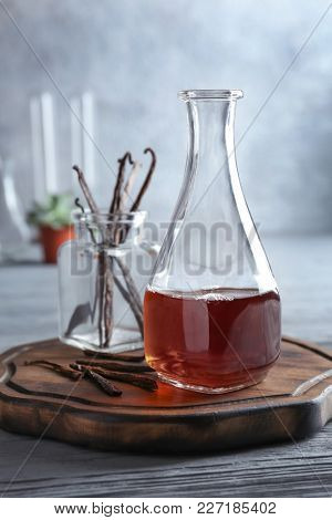 Bottle with vanilla extract and sticks on wooden board