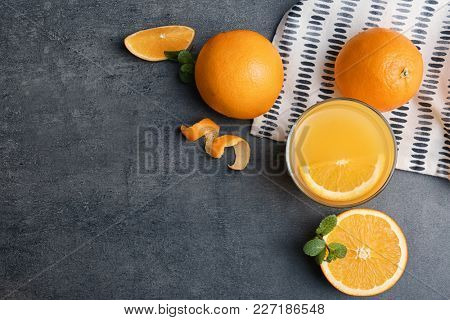 Beautiful composition with fresh orange juice and fruit on grey background