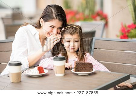 Young Woman Telling A Secret To Her Daughter While Sitting At Restaurant Table With Cake And Coffee