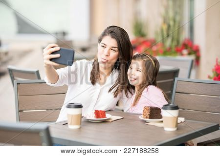 Funny Mother And Daughter Sticking Out Tongue And Taking Selfie With Mobile Phone At A Cafe