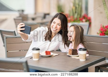 Cheerful Young Woman With Her Little Girl  Sitting At A Cafe And Taking Selfie With Smart Phone