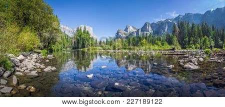 Panoramic View Of Famous Yosemite Valley With Beautiful Merced River On A Scenic Sunny Day With Blue