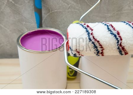 Tin Can Of Pink Oil Paint, A Roller Paint And A Brush Against A Light Concrete Wall, Close Up