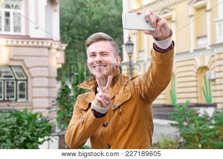 Young handsome man taking selfie outdoors